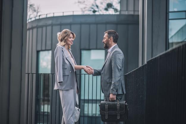 ビジネスパートナー。ブリーフケースと笑顔の女性と午後にオフィスビルの近くで握手するビジネスひげを生やした男性