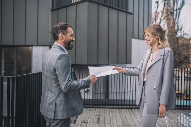 ビジネスパートナー。ビジネスの楽しい大人の男性と若い女性がオフィスの近くで屋外でドキュメントを保持している