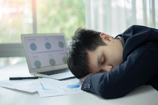 비즈니스 파트너는 오랜 시간 일한 후 노트북과 문서를 들고 책상에서 자고 있는 남성 젊은 사업가를 개념으로 합니다.