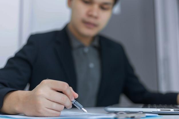 비즈니스 파트너는 문서 형식으로 표시된 최근 달의 이익 요약을 가리키는 펜을 들고 있는 젊은 사업가를 개념으로 합니다.