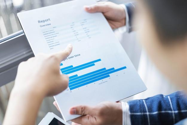 비즈니스 파트너는 문서 형식으로 표시되는 최근 달의 판매 요약을 수정하는 젊은 사업가를 개념으로 합니다.