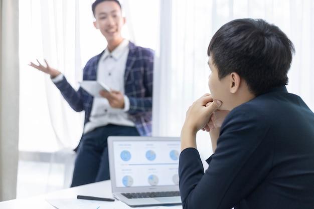 비즈니스 파트너는 새로운 다가오는 제품의 마케팅 계획에 대해 동료와 이야기하는 젊은 사업가를 개념으로 합니다.