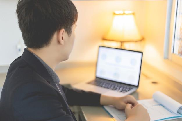 비즈니스 파트너는 연간 판매 요약을 수정하는 노트북을 사용하는 젊은 사업가를 개념으로 합니다.