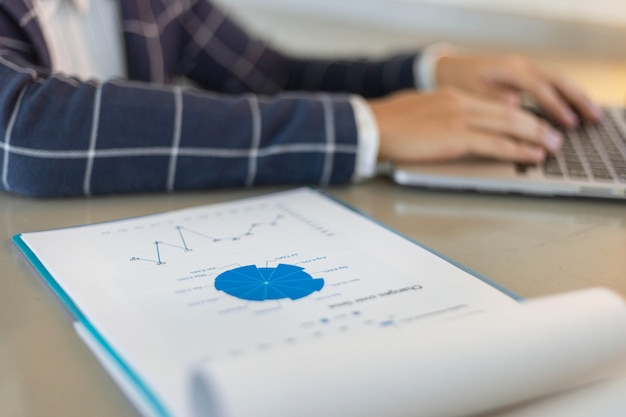 Деловые партнеры концепции молодой бизнесмен, используя ноутбук, пересматривая сводку годовых продаж.