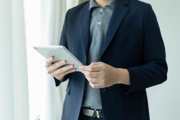 비즈니스 파트너는 이메일 받은 편지함을 확인하는 태블릿 화면을 보고 있는 해군 정장 재킷을 입은 젊은 사업가를 컨셉으로 합니다.
