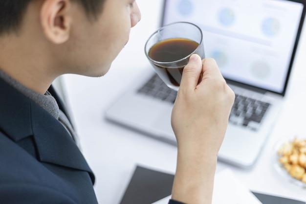 Деловые партнеры концепции молодого мужчины-предпринимателя, держащего чашку черного кофе, сидя с ноутбуком, посещая ежемесячное собрание.