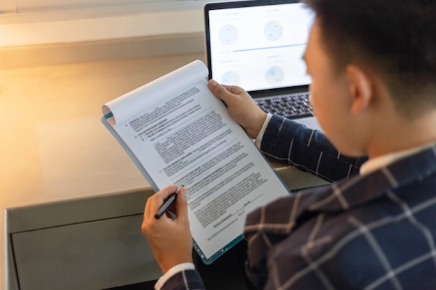 Business partners concept a young businessman revising sales summary of the recent month showing in document forms.