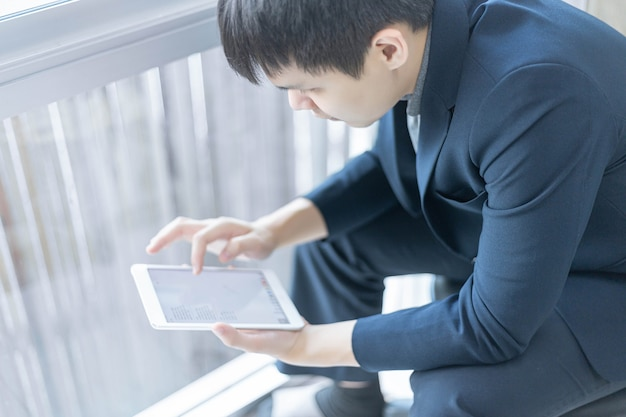 Business partners concept a young businessman wearing navy suit jacket looking on the tablet screen checking an email inbox.