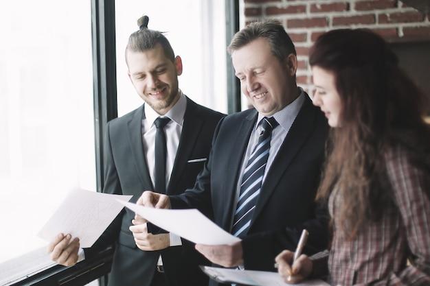Деловые партнеры обсуждают деловые документы, стоя в офисе