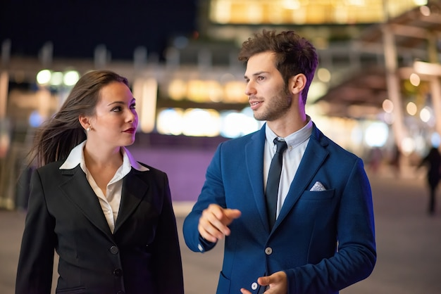 Business partners discussing together late in the evening in a modern city setting