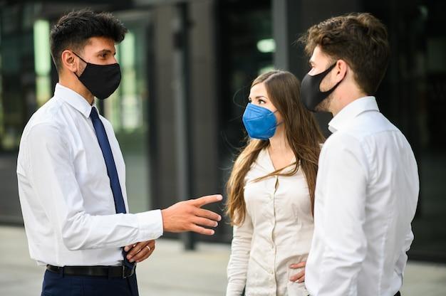 Covid19コロナウイルスパンデミックに対する保護マスクを身に着けて屋外で一緒に議論するビジネスパートナー