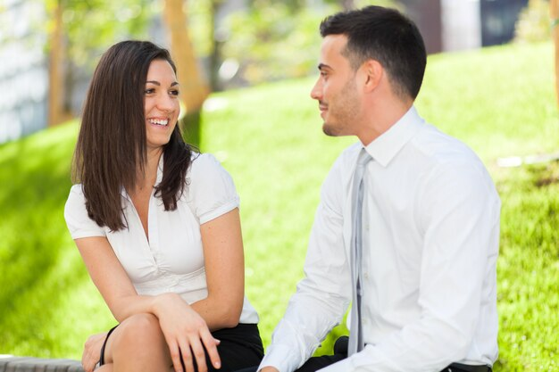 Business partners discussing while sitting on a bench outdoor