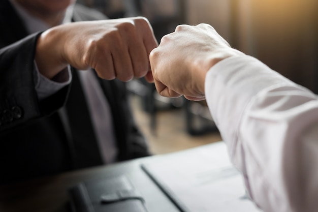 Business partners giving fist bump to commitment