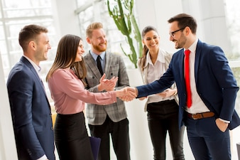 Business partners handshaking after making agreement with employees near by