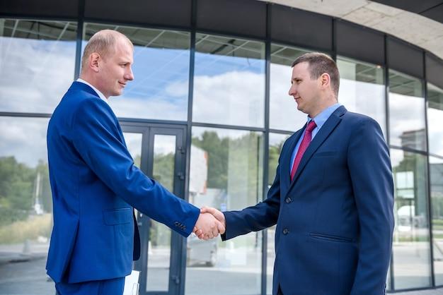 屋外の大きな建物の前に握手するビジネスパートナー