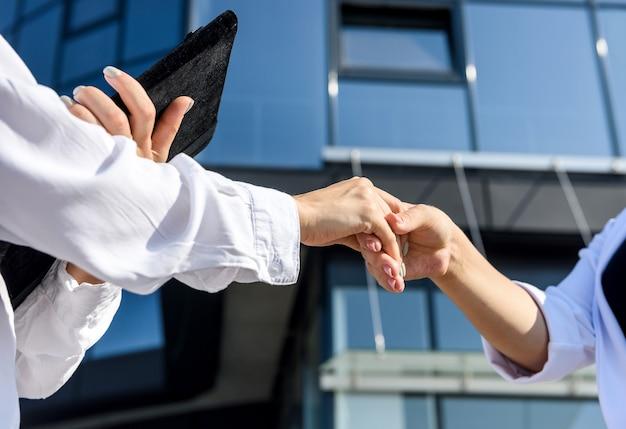オフィスビルの前に握手するビジネスパートナー。ビジネススーツを着た2人の美しい女性がお互いに笑顔