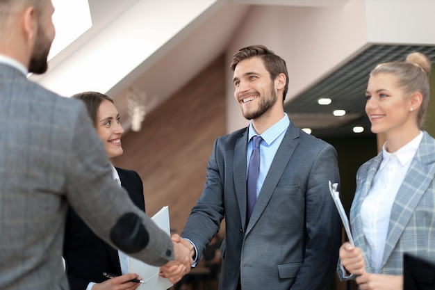 Business partners handshaking over business objects on workplace.