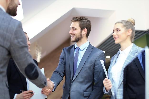 Деловые партнеры, рукопожатия над бизнес-объектами на рабочем месте.