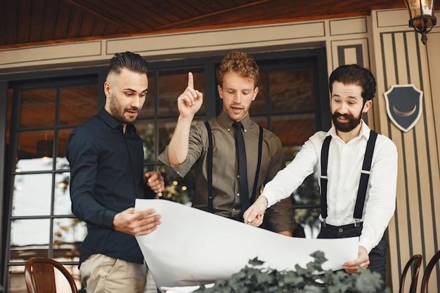 Деловые партнеры проводят обсуждения. говорят мужчины в деловых костюмах. мужчина в подтяжках с бородой.