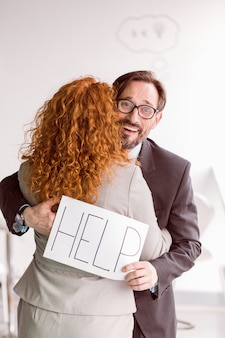 Business partners hugging, man asking for help with board.