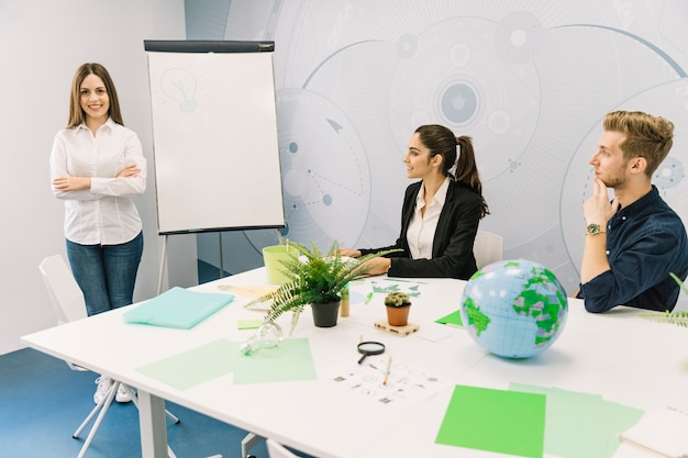 Business partners looking at female manager standing with folded hands near flipchart