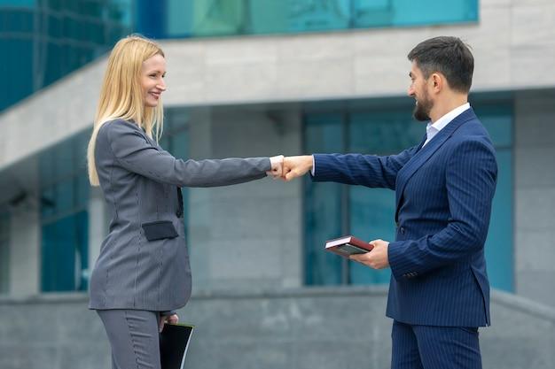 비즈니스 파트너 남자와 여자는 그들의 손으로 서로 인사