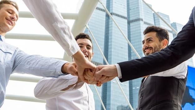 ビジネスパートナーは拳をサークルフィストバンプに入れます。チームビルディング、サポート、相乗効果