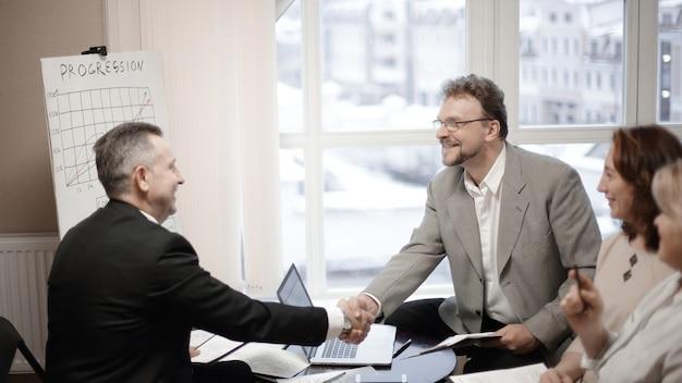 Деловые партнеры, пожимая руки перед деловой встречей в офисе