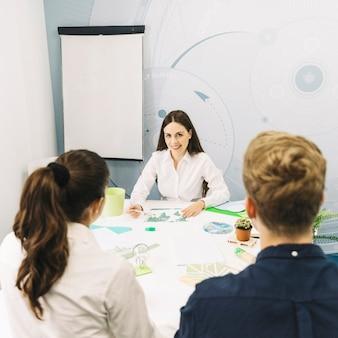 Деловые партнеры, сидя перед улыбается женщина-менеджер на рабочем месте