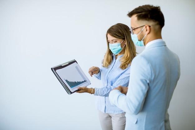 Деловые партнеры, стоящие и смотрящие на бизнес-результаты в офисе, в защитных масках от вирусов