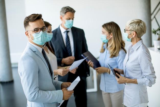 フェイスマスクを着用している間、ビジネスパートナーが立ってビジネスの結果をオフィスで見ているウイルス保護
