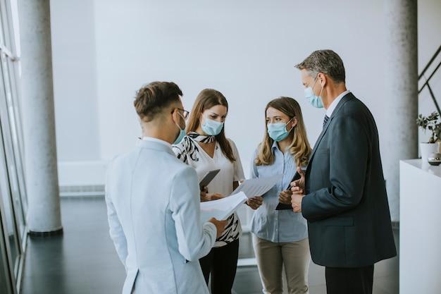 Деловые партнеры стоят и смотрят на бизнес-результаты в офисе, надевая защитные маски от вирусов