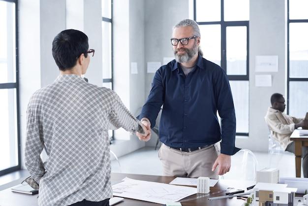 Деловые партнеры стоят и пожимают друг другу руки за столом, чтобы заключить договор в офисе