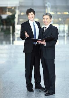 Деловые партнеры с документами, стоящими в офисе