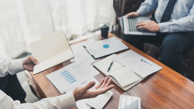 Деловые партнеры, работающие с портативным компьютером, анализируя финансовый результат проекта