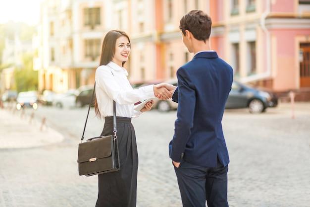 Технологии делового партнерства и люди концепции улыбающегося рукопожатия бизнесмена и деловых женщин