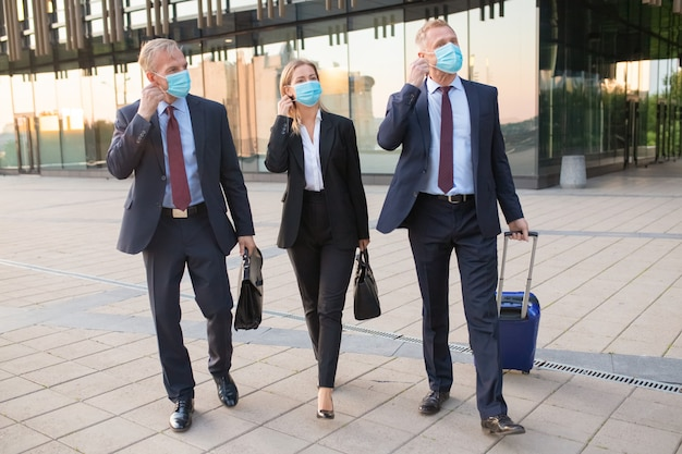 Business people adjusting or ready to take off face masks while walking with luggage outdoors, near office buildings. business trip and end of epidemic concept