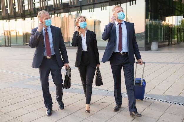 Uomini d'affari che si adattano o sono pronti a togliersi le maschere mentre camminano con i bagagli all'aperto, vicino a edifici per uffici. viaggio di lavoro e fine del concetto di epidemia