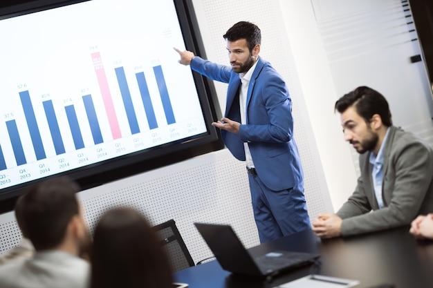 Деловые люди анализируют данные на встрече в офисе и делают статистику
