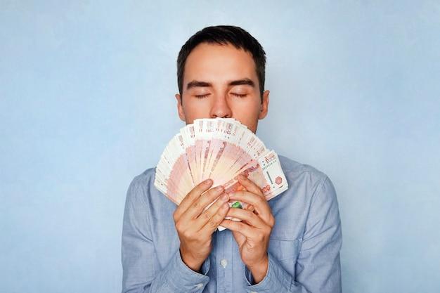 비즈니스, 사람, 재정 개념 - 러시아 돈 냄새가 나는 사업가. 달콤한 돈 냄새. 5000 루블을 스니핑하는 젊은 남자 돈을 벌었습니다. 샐러리. 쉽게 벌리는 돈.