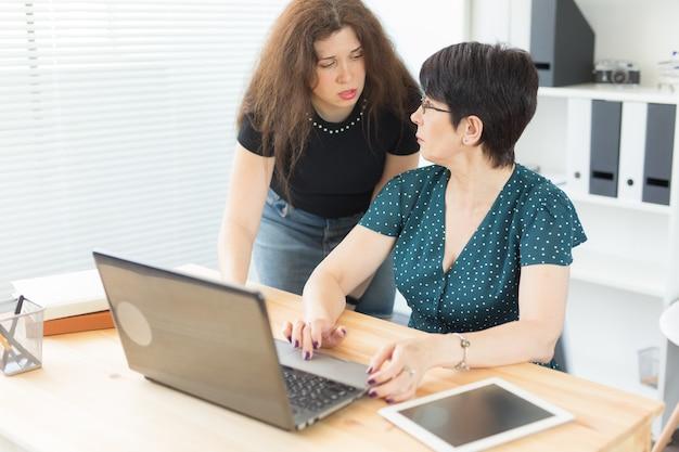 사업가와 그래픽 디자이너 개념 - 여성들은 사무실에서 노트북으로 아이디어를 논의하고 화면을 가리키고 있습니다.
