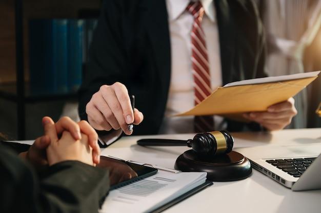 비즈니스 사람과 변호사는 테이블에 앉아 계약 서류를 논의합니다. 법률, 조언, 법률 서비스의 개념. 아침 햇살에