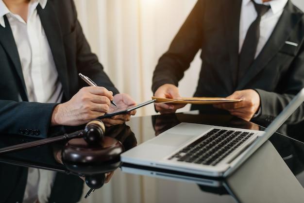 사업가들과 변호사들이 탁자에 앉아 계약서에 대해 토론하고 있습니다. 법률, 조언, 법률 서비스의 개념. 아침 햇살에