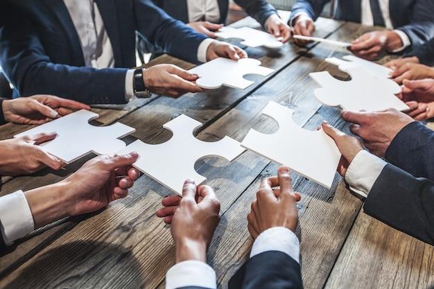 비즈니스 사람과 나무 테이블, 팀워크 개념에 퍼즐
