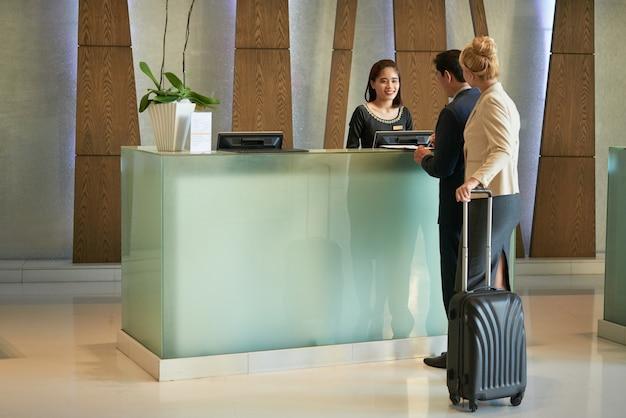 비즈니스 센터 건물 또는 호텔의 현대적인 로비에서 비즈니스 사람들과 접수원