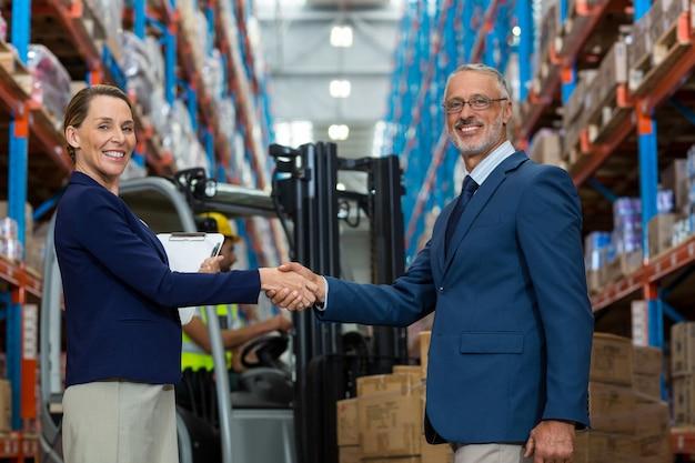 Деловые люди рукопожатие и смотрит в камеру перед рабочими
