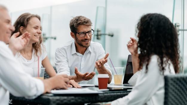비즈니스 사람들이 비즈니스 센터 로비에 있는 테이블에 앉아 이야기하고 있다