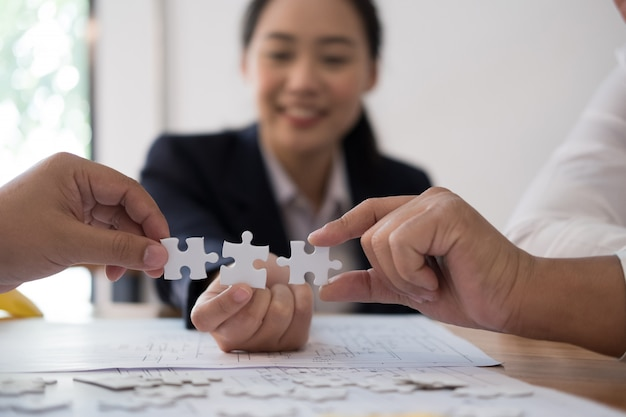 Business people assembling piece of puzzle together
