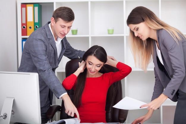 アイデアを共有し、オフィスで働く会議でのビジネスマン。会議テーブルに座って、一緒にプロジェクトに取り組んで、コンピューターモニターを見ているビジネスチーム。高解像度。