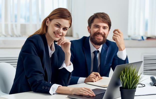 ノートパソコンの感情モデルマネージャーインテリアスーツとテーブルでビジネスマン